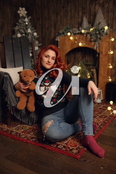 Attractive happy young woman in cozy comfortable clothes is sitting near a Christmas tree decorated with shiny toys among gold and red New Year's gifts. Magical festive atmosphere. Cute girl.