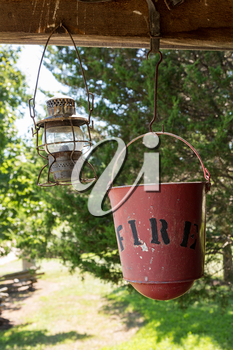 Old worn fire bucket and oil lamp hanging from rafters of log cabin