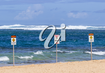 Three warning sign no swimming and strong currents in treacherous winter waters on Tunnels Beach in Kauai Hawaii