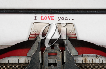 Macro detail of the ink ribbon and text of I Love You on electric typewriter for greeting card