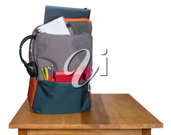 Backpack filled with back to school supplies on a wooden table and isolated against white background