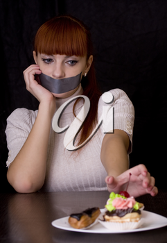 The girl, whose mouth sealed with tape extends at plate with cakes
