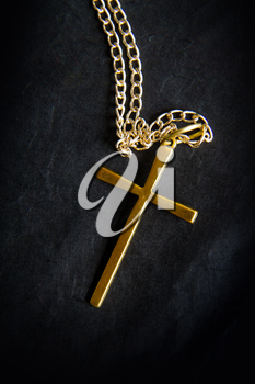 a simple metal cross on a chain lies against a black background
