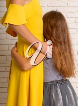 The little girl gently pressed and hugs her mom in a bright dress