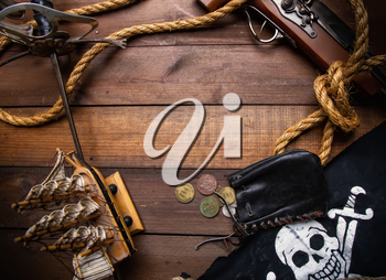 Background of several pirate items lying on a dark wooden surface forming a frame