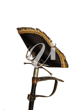 Classic pirate black felt captain's cocked hat hanging on an old scabbard in a scabbard isolated on a white background