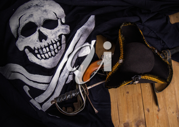 Classic pirate black felt captain's cocked hat with a pistol and a sword lying on a wooden floor next to the Jolly Roger flag