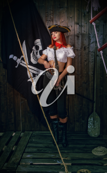Young attractive armed girl pirate captain looks into the distance on the background of the flag Jolly Roger