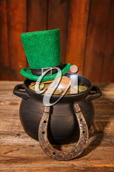 Treasure in a black pot and a green leprechaun hat on a wooden table next to a horseshoe symbol of good luck