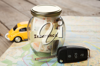 Car finance concept - money glass with word Insurance, car key and roadmap