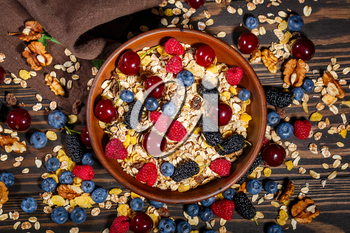 Fresh summer berries and a bowl of muesli on a dark wooden background