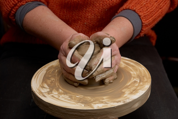 Female hands forming clay pot on the pottery wheel