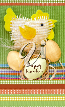 Easter composition with eggs and handmade toy chicken on a green and ornamental cloth.