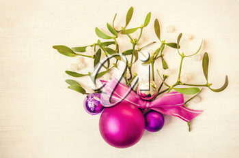 New Years and Christmas decorations with mistletoe on wooden background. Nature background.