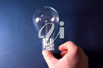 Incandescent lamp in the hand. Lamp is the source of lighting.