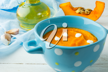 Creamy pumpkin squash vegetable soup with cream in a blue bowl on white wooden background