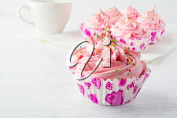 Pink delicious cupcakes and cup of tea. Birthday cupcakes. Homemade cupcake. Sweet cupcake. Gourmet cupcakes. Sweet dessert. Sweet pastry.