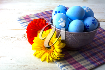 Blue Easter eggs in a purple bowl and flower on a white wooden background. Easter background. Easter eggs. Easter. Easter hunt. Easter symbol.  Easter card. Easter greetings. Happy Easter