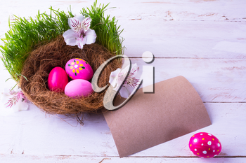 pink Easter eggs in a nest with white flowers in the green fresh grass on the white wooden background with natural unbleached paper for congratulation. Easter background. Easter symbol. Copy space