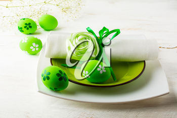 Green Easter table place setting with plate, napkin and Green Decorated Easter eggs on white wooden background