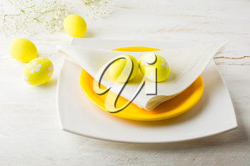 Yellow Easter table place setting with plate, napkin and Yellow Decorated Easter eggs on white wooden background