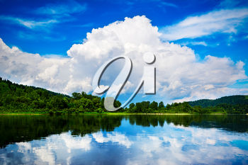 Beautiful landscape of the island and the blue sky with white clouds reflected in the clear water. Wooded shore of a mountain lake. Summer idyllic landscape.