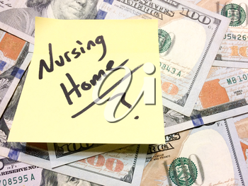 American cash money and yellow paper note with text Nursing Home with question mark in black color aerial view