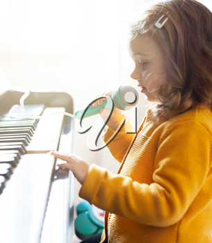 Girl toddler plays the piano and sings with the toy microphone.