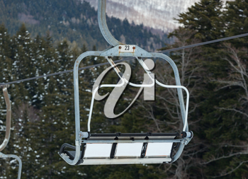 Chair lift on over the snowy forest at Abetone, Italy.