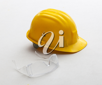 Yellow helmet and glasses for work safety on plasterboard panels.